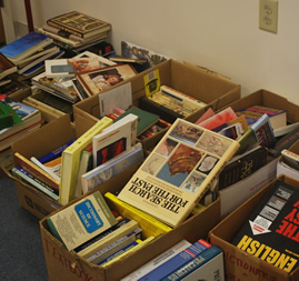 piles of books stored in boxes ready to be scanned